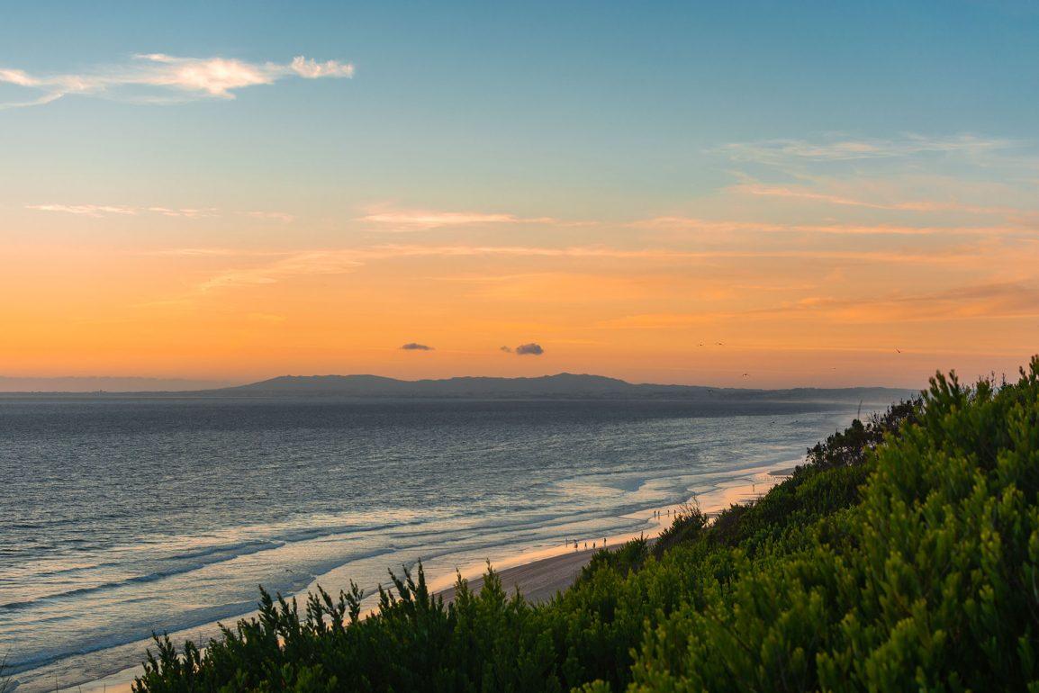 Praia da Adiça: Green vegetation, a calm sea, and an orange sunset over the Atlantic ocean