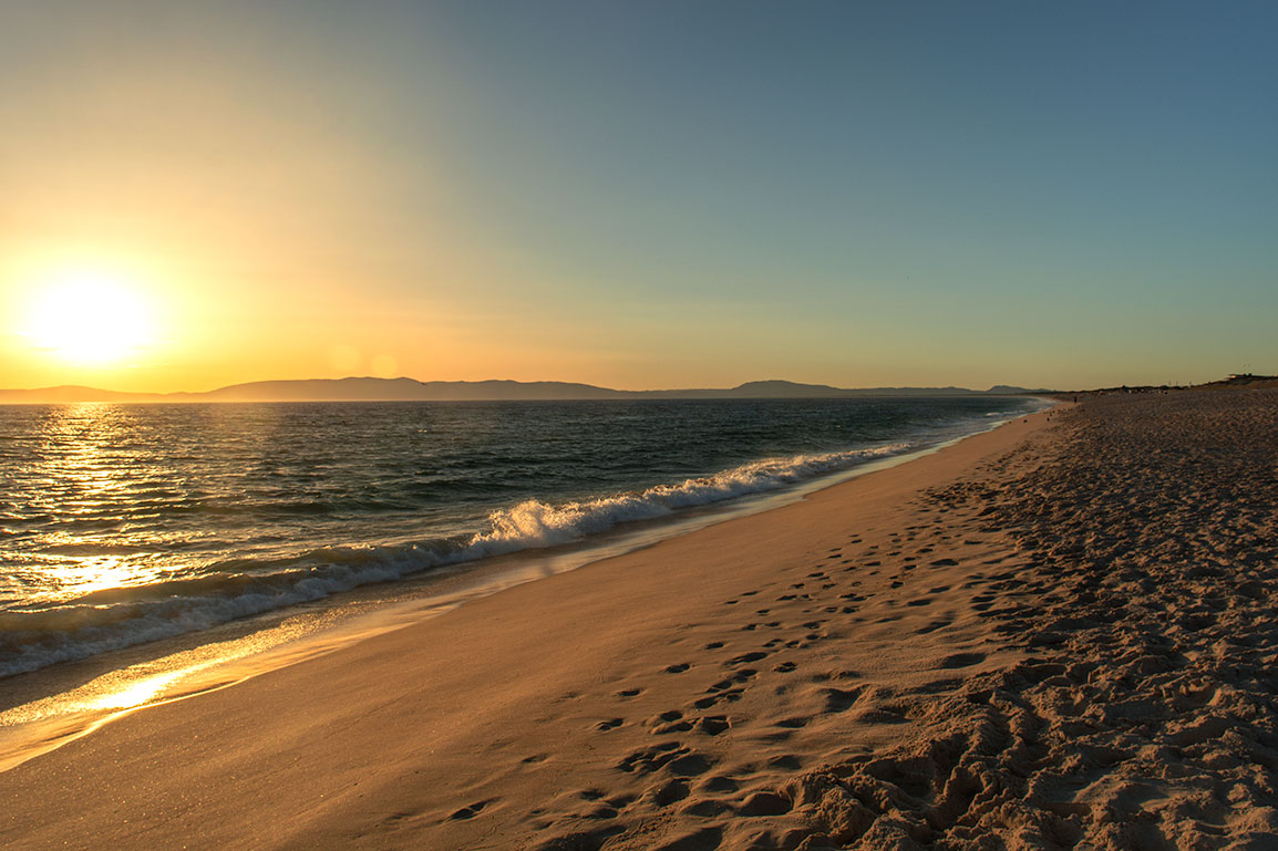 Photo of Praia da Comporta: an empty beach, golden fine sand, a small wave, and the sun setting