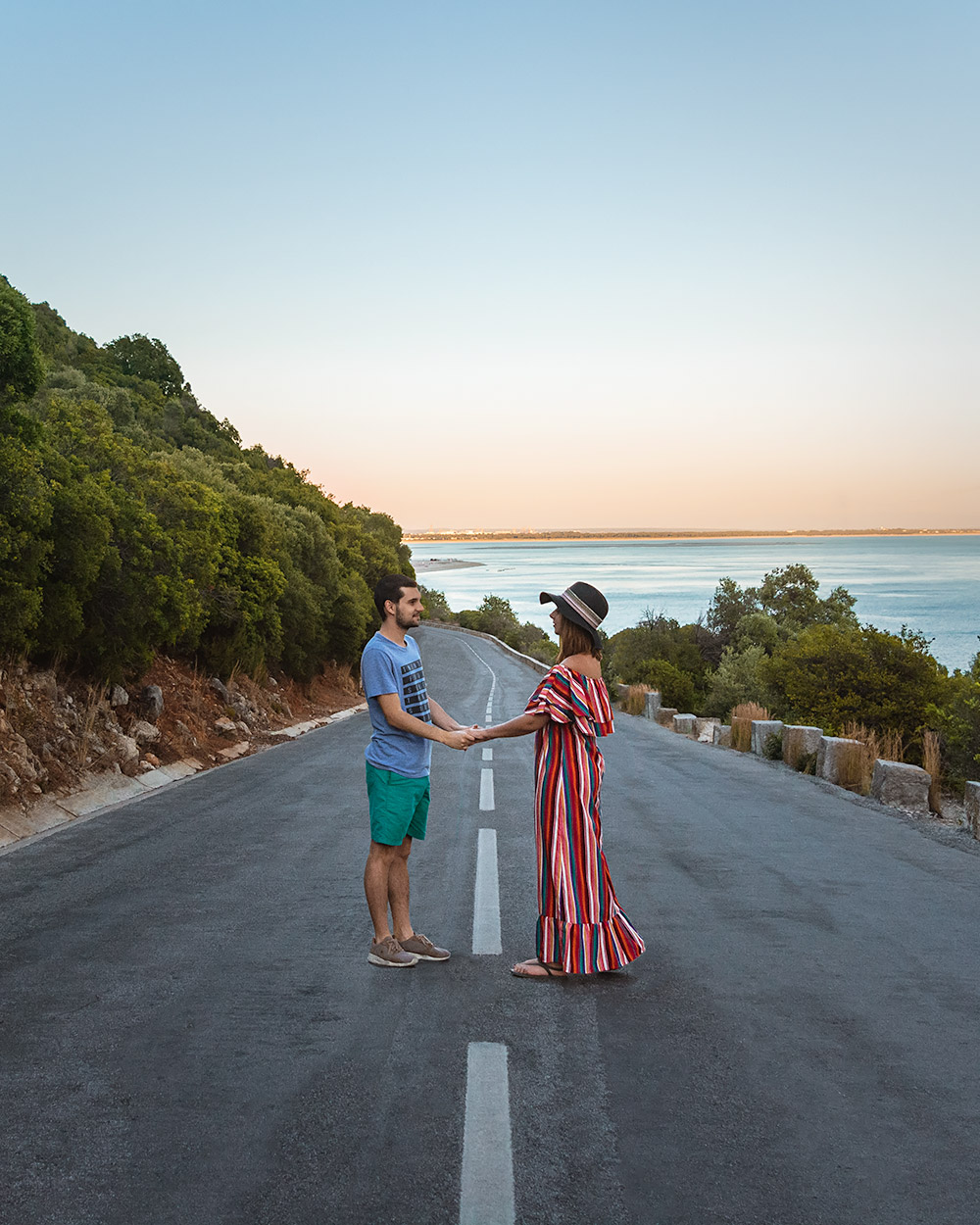 Maria and Rui in the middle of an empty road by the beautiful Arrabida Park in Portugal