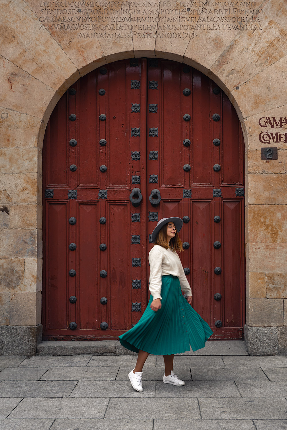 Maria dancing in the front of a pretty door in Salamanca, Spain
