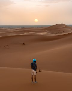 Rui posing in the dunes of Morocco's desert during a beautiful sunset