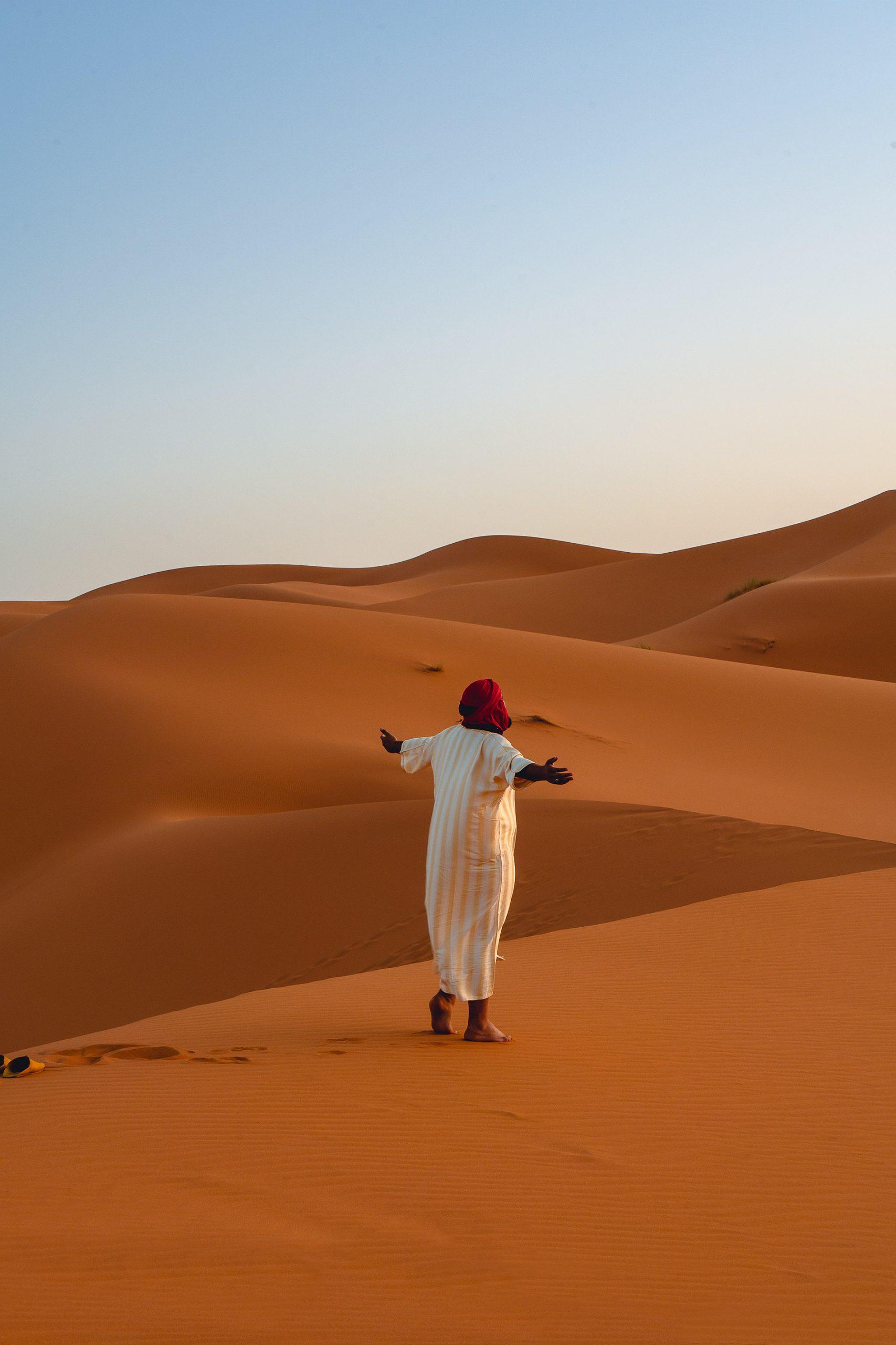 Enjoying the sunrise in the Egg Chebbi sand dunes in the desert of Morocco
